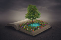 Oasis on top of a book. A beautiful flower and water oasis on top of a book stock photo