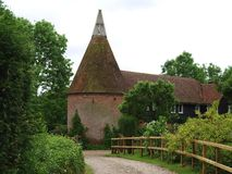 Oast House. In the english countryside with pathway and bordering trees Royalty Free Stock Image