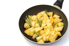 Oasted potatoes with rosemary in frying pan. Roasted potatoes with rosemary in frying pan, white background, soft shadows Stock Photos