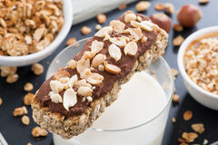 Oat bar with chocolate and nuts, a glass of milk, close-up Royalty Free Stock Images