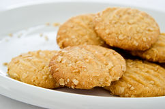 Oat Biscuits on White China Plate. Crumbly oat biscuits (cookies) on a white china plate with crumbs visible royalty free stock image