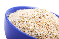 Oat bran. Bowl of oat bran on white background. It is common ingredient of healthy meal Stock Image