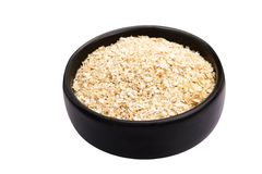 Oat bran. Bowl of oat bran on white background. It is common ingredient of healthy meal Stock Photography