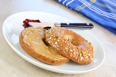 Oat bran bagel and peanut butter. Stock Photography