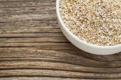 Oat bran. A ceramic bowl on grained wood background Royalty Free Stock Image