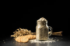 Oat bunch, cookies and flakes in flavouring jar. Isolated on black background. Grain bouquet, golden oats spikelets on dark wooden table, can filled with dried Royalty Free Stock Photos