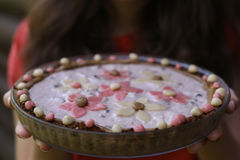 Oat cacke with jogurt topping and marzipan flowers. On the top hand hold royalty free stock photography