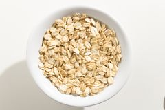 Oat cereal grain. Top view of grains in a bowl. White background Royalty Free Stock Image