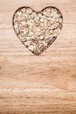 Oat cereal heart shaped on wooden surface. Stock Image