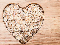 Oat cereal heart shaped on wooden surface. Royalty Free Stock Photography