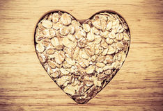Oat cereal heart shaped on wooden surface. Stock Images