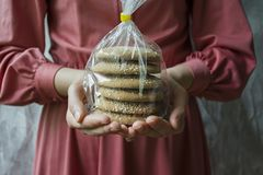Oat cookies. A girl is holding a package with oatmeal cookies. Closeup front view royalty free stock photos