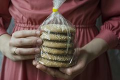 Oat cookies. A girl is holding a package with oatmeal cookies. Closeup front view stock images