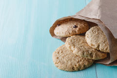 Oat cookies in paper bag on wood table Royalty Free Stock Photo