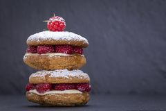 Oat cookies with raw raspberry, honey and soft cheese on the background of black slate , close up Royalty Free Stock Images