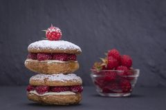 Oat cookies with raw raspberry, honey and soft cheese on the background of black slate , close up Royalty Free Stock Photo