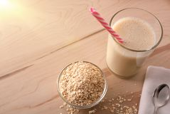 Oat drink in glass and cereal flakes top view stock image