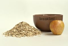 Oat flakes, apple and a cup for breakfast royalty free stock photos