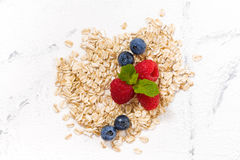 Oat flakes and berries on a white background, top view Royalty Free Stock Images
