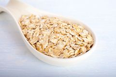 Oat flakes in big porcelain spoon on white background royalty free stock photography