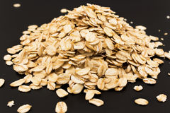 Oat flakes on a black background Royalty Free Stock Photo