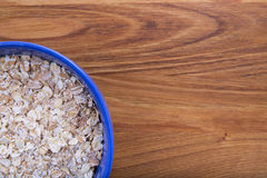 Oat flakes in a blue plate on a dark wood Royalty Free Stock Photos