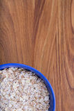 Oat flakes in a blue plate on a dark wood Stock Photos