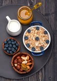 Oat flakes, blueberries, nuts, honey and milk. Fitness breakfast. Stock Photography