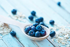 Oat flakes and blueberry. Raw oat flakes and fresh blueberry on a table Stock Photo