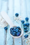 Oat flakes and blueberry. Raw oat flakes and fresh blueberry on a table Royalty Free Stock Image