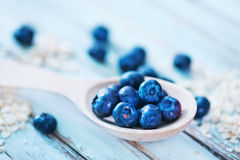 Oat flakes and blueberry. Raw oat flakes and fresh blueberry on a table Stock Photography