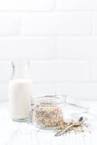 oat flakes and bottle of milk and white background, vertical Royalty Free Stock Photos