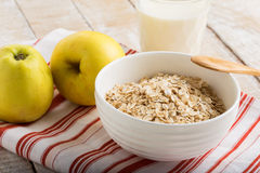 Oat flakes in bowl with apple and milk Stock Images