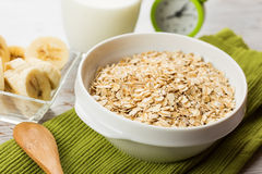 Oat flakes in bowl with banana and milk Royalty Free Stock Images