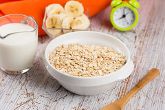 Oat flakes in bowl with banana and milk Stock Photography