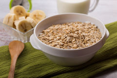 Oat flakes in bowl with banana and milk Royalty Free Stock Photo