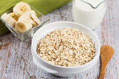 Oat flakes in bowl with banana and milk Stock Image