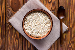 Oat flakes in a bowl on a napkin and a wooden spoon Stock Photo