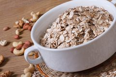 Oat flakes in a bowl and scattered on the table nuts. Stock Images
