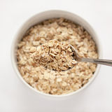 Oat flakes in bowl and spoon. On white background stock image