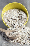 Oat flakes in bowl with wooden spoon Stock Photography