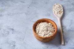 Oat flakes in bowl and wooden spoon on wooden background, close-up, top view, selective focus. Royalty Free Stock Images