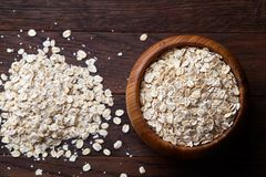 Oat flakes in bowl and wooden spoon on wooden background, close-up, top view, selective focus. Stock Images