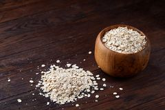 Oat flakes in bowl and wooden spoon  on wooden background, close-up, top view, selective focus. Stock Photos