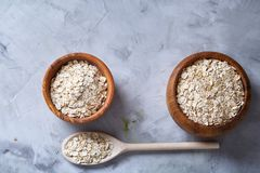 Oat flakes in bowl and wooden spoon isolated on wooden background, close-up, top view, selective focus. Royalty Free Stock Photo