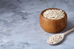 Oat flakes in bowl and wooden spoon on wooden background, close-up, top view, selective focus. Stock Photo