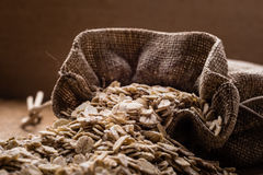 Oat flakes cereal in burlap sack on wooden table. Royalty Free Stock Images