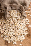 Oat flakes cereal in burlap sack on wooden table. Stock Photo