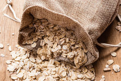 Oat flakes cereal in burlap sack on wooden table. Royalty Free Stock Image