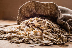 Oat flakes cereal in burlap sack on wooden table. Stock Images